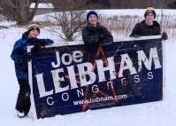 Boys find discarded political sign and carry it from ditch to cabin!